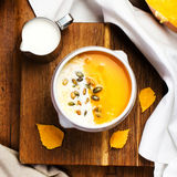 Pumpkin Soup with whipped cream and pumpkin seeds in a white pla Stock Photo
