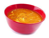 Pumpkin Soup on White. Pumpkin soup in a red bowl, swirled with cream and sprinkled with cumin seeds, on white Royalty Free Stock Photography