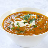 Pumpkin Soup. In white bowl over brocade background.  Topped with yogurt and parsley Stock Photography
