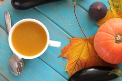 Pumpkin soup in white mug on blue table. Harvest composition. Stock Photo