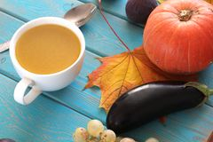 Pumpkin soup in white mug on blue table. Harvest composition. Stock Photos