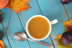 Pumpkin soup in white mug on blue table. Harvest composition. Royalty Free Stock Photography