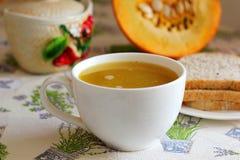 Pumpkin soup in white mug on table. Stock Photos