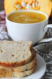 Pumpkin soup in white mug on table. Stock Image