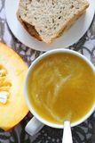 Pumpkin soup in white mug on table. Royalty Free Stock Images