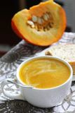 Pumpkin soup in white mug on table. Royalty Free Stock Photo