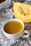Pumpkin soup in white mug on table. Royalty Free Stock Photos