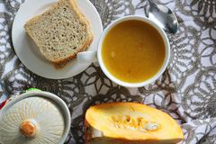 Pumpkin soup in white mug on table. Stock Photo