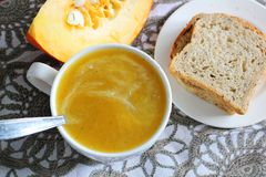 Pumpkin soup in white mug on table. Royalty Free Stock Photography