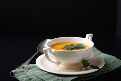 Pumpkin soup in white plate on black background Royalty Free Stock Photo