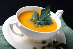Pumpkin soup in white plate on black background Royalty Free Stock Image