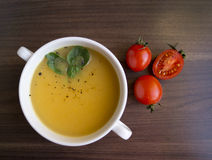The pumpkin soup. Pumpkin soup in white plate with tomatoes Royalty Free Stock Image