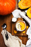 Pumpkin Soup With Whipped Cream And Pumpkin Seeds In A White Plate Over Wooden Background. Beautiful Autumn Pumpkin Thanksgiving Stock Photos