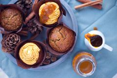 Pumpkin spice cupcake with buttercream and pumpkin sirup next to muffin on concrete grey round tray on blue napkin Stock Photo