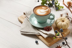 Pumpkin spice latte. Coffee cup on white wood background stock photo