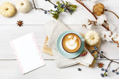 Pumpkin spice latte. Coffee top view on white wood background Stock Photos