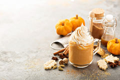 Pumpkin spice latte in a glass mug. With cinnamon, nutmeg and cookies Royalty Free Stock Photo