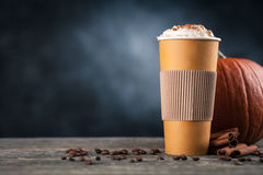 Pumpkin spice latte in a paper cup. On dark background Stock Photos