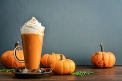 Pumpkin spice latte. With whipped cream on wooden background royalty free stock image