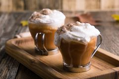 Pumpkin spice latte with whipped cream and pie spices. Pumpkin spice latte topped with whipped cream and pumpkin pie spices, traditional fall favorite beverage stock photos