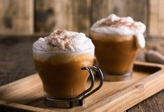Pumpkin spice latte with whipped cream and pie spices. Pumpkin spice latte topped with whipped cream and pumpkin pie spices, traditional fall favorite beverage royalty free stock photo