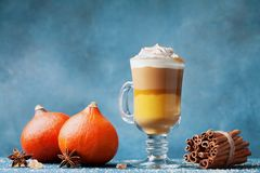 Pumpkin spiced latte or coffee in glass on dark blue table. Autumn, fall or winter hot drink. stock photography