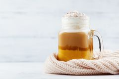 Pumpkin spiced latte or coffee in glass jar decorated knitted scarf on white wooden table. Autumn, fall or winter hot drink. royalty free stock photos