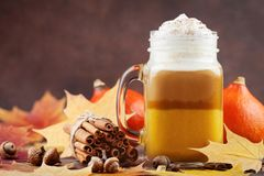 Pumpkin spiced latte or coffee in glass jar decorated leaves on brown table. Autumn, fall or winter hot drink. stock image