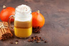 Pumpkin spiced latte or coffee in glass jar on brown table. Autumn, fall or winter hot drink. Stock Photography