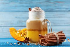 Pumpkin spiced latte or coffee in glass jar on turquoise wooden table. Autumn, fall or winter hot drink. stock photos