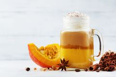Pumpkin spiced latte or coffee in glass jar on white wooden table. Autumn, fall or winter hot drink. stock photo