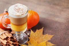 Pumpkin spiced latte or coffee in glass on brown table. Autumn, fall or winter hot drink. stock photos