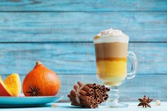 Pumpkin spiced latte or coffee in glass on turquoise rustic table. Autumn, fall or winter hot drink. royalty free stock images