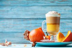 Pumpkin spiced latte or coffee in glass on turquoise wooden table. Autumn, fall or winter hot drink. Royalty Free Stock Image