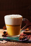 Pumpkin spiced latte or coffee in a glass on a wooden table. Autumn or winter hot drink. Stock Photography