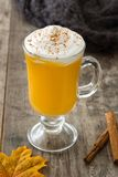 Pumpkin spiced latte on wooden table. Typical halloween drink Stock Photos