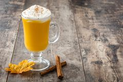 Pumpkin spiced latte on wooden table. Typical halloween drink Stock Image