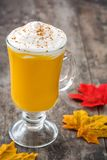 Pumpkin spiced latte on wooden table. Typical halloween drink. Copyspace Stock Photo