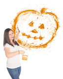 Pumpkin Splatter. A pretty preteen flinging orange paint to create a splattered Halloween pumpkin.  On a white background with plenty of space below the pumpkin Royalty Free Stock Photography