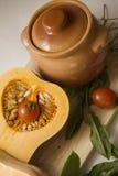 Pumpkin stew. Raw Pumpkin on cutting board with clay pot Stock Photos