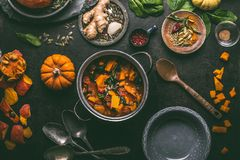Pumpkin stew with spinach and ginger in cooking pot with spoon and bowl on dark kitchen table background Royalty Free Stock Image