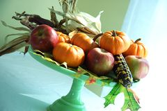 Pumpkin still life 2. Pumpkins, indian corn and fall leaves on a cake pedestal royalty free stock image