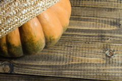 Pumpkin in straw hat Stock Images