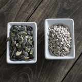 Pumpkin and sunflower  seeds on a wooden Board Stock Images