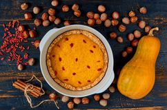 Pumpkin tart with goji berry in the baking dish decorated with hazelnuts on wooden background. Traditional pie for Thanksgiving. Pumpkin tart with goji berry in royalty free stock photos