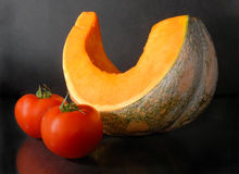 Pumpkin and  tomatoes. Half of pumpkin and two tomatoes on a dark background Royalty Free Stock Photo
