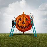 Pumpkin Tree Concept. With a witch and mummy monster trimming an orange jack o lantern plant as a halloween celebration symbol for a festive autumn tradition Royalty Free Stock Image