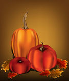 Pumpkin trio with oak leaves. Three orange pumpkins with oak leaves on a warm golden background Royalty Free Stock Image