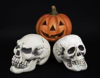 Pumpkin and Two Skulls Stock Photos