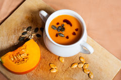 Pumpkin vegetable cream soup in white bowl with piece pumpkin Stock Images